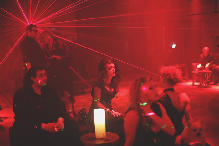 Atmospheric nightclub portrait of party goers sitting and chatting