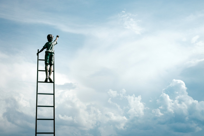 A creative shot of a child on top of a ladder against a blue sky