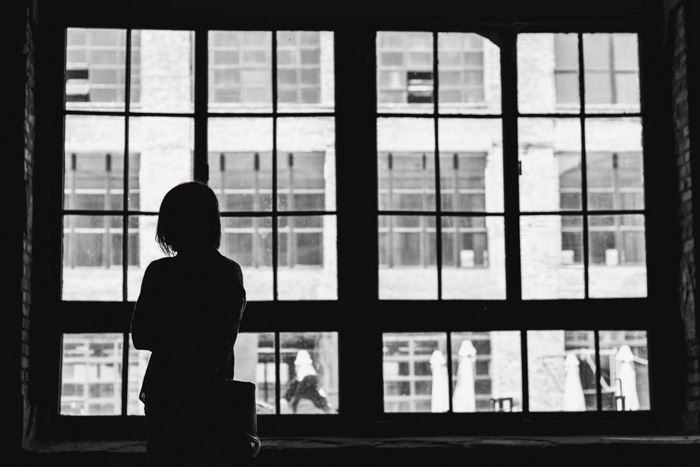 A black and white photo of a girl looking out a window - photography lingo