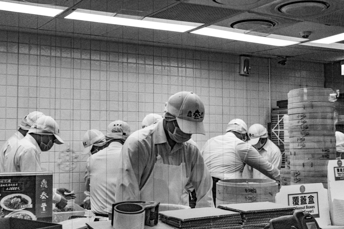 A candid black and white photo of workers in a fast food restaurant - photography slang