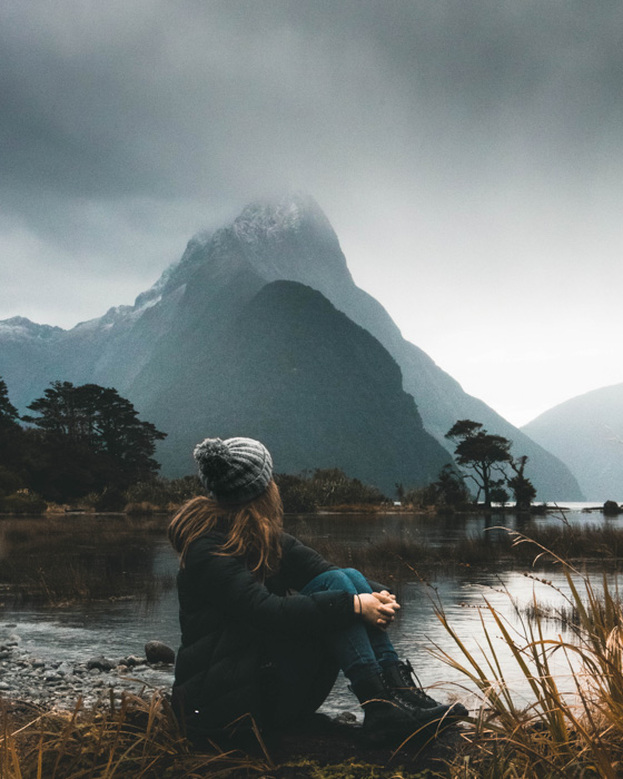 Atmospheric porttrait of a female model sitting by a lake and mountainous landscape - photography slang