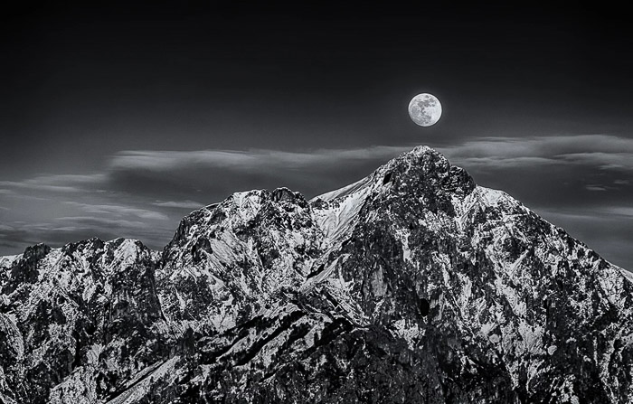 Black and white shot of the full moon over a stunning mountainous landscape