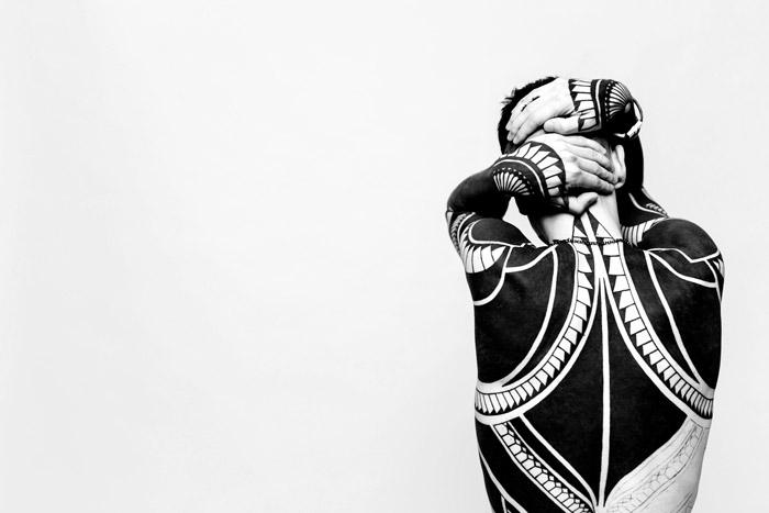 Una modelo tatuada frente a una pared blanca - fotos abstractas del cuerpo