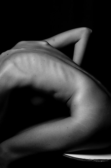 A black and white abstract body photography shot using lines to create balance and divide space