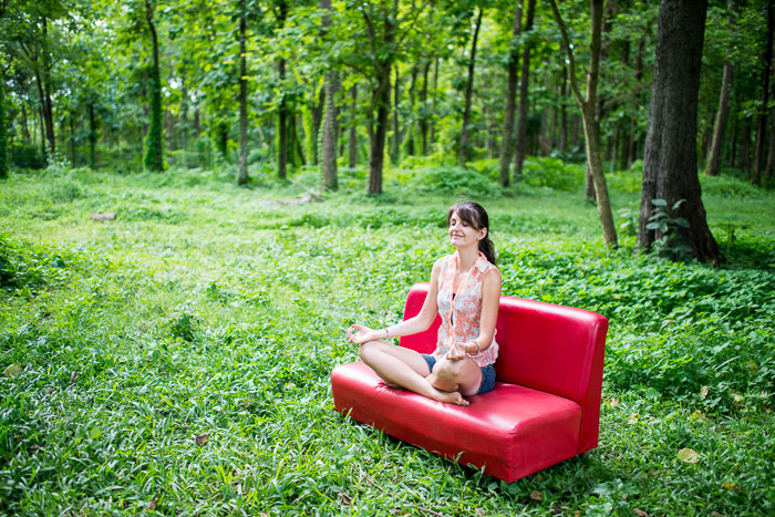 A female model meditating on a red couch in a forest