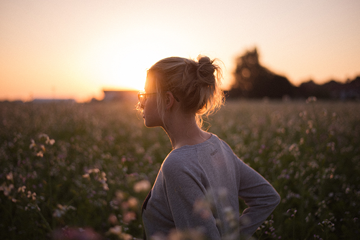 A candid portrait of a female model in a meadow at sunset