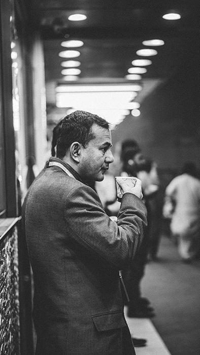 A black and white candid street photography shot of a man drinking coffee at a railway station