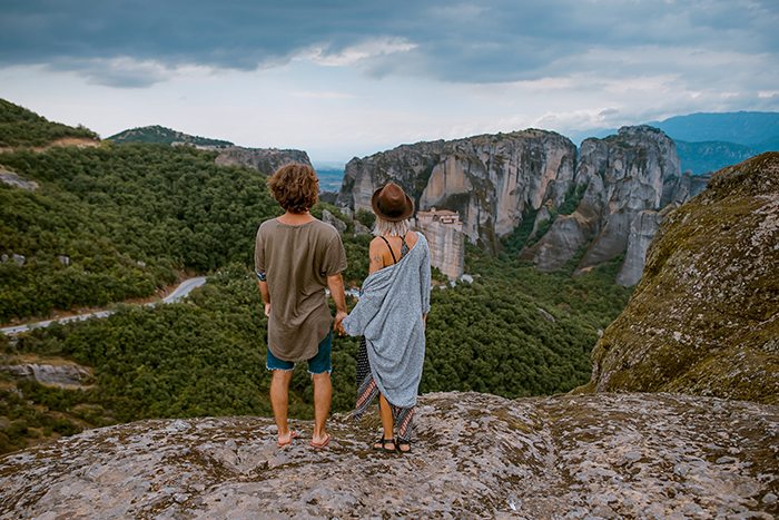 A candid photography example of couple holding hands in a picturesque landscape
