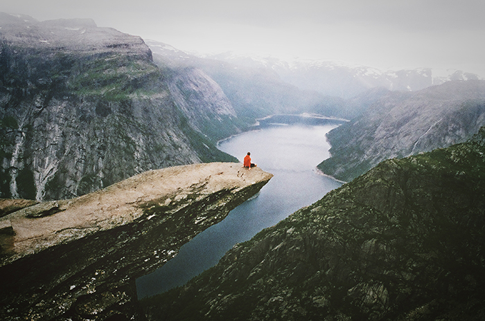 A candid photography example ofa  person sitting on a cliff overlooking a stunning mountainous landscape