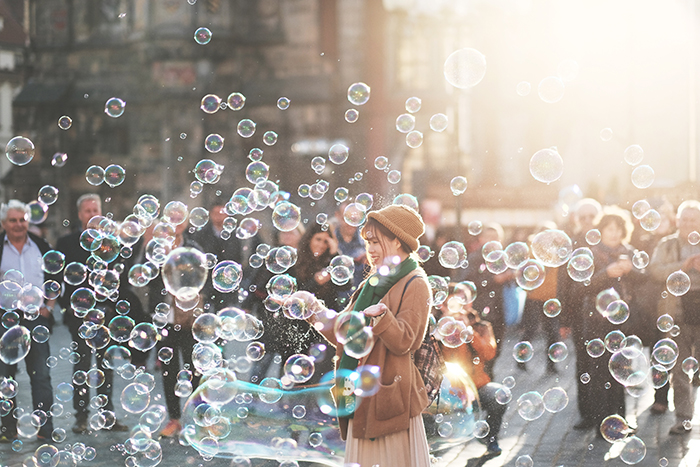A street photography shot of a woman playing with bubbles outdoors