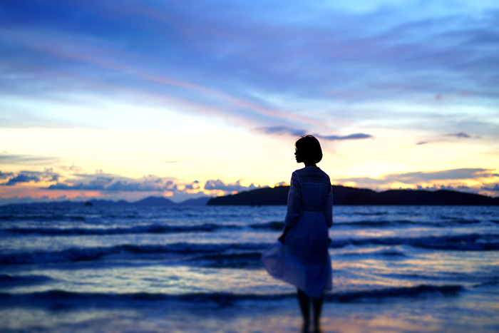A candid photography example of of a woman on a beach at night