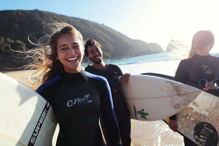 A candid photography example of group of surfers smiling on the beach