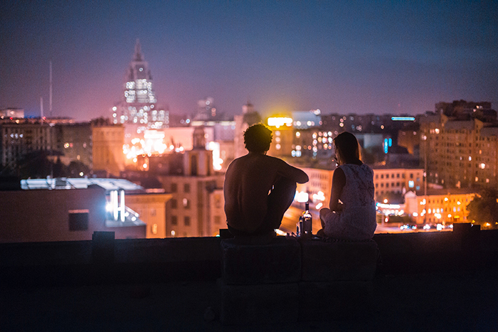 A candid photography example of a couple sitting on the roof of a tall building at night -