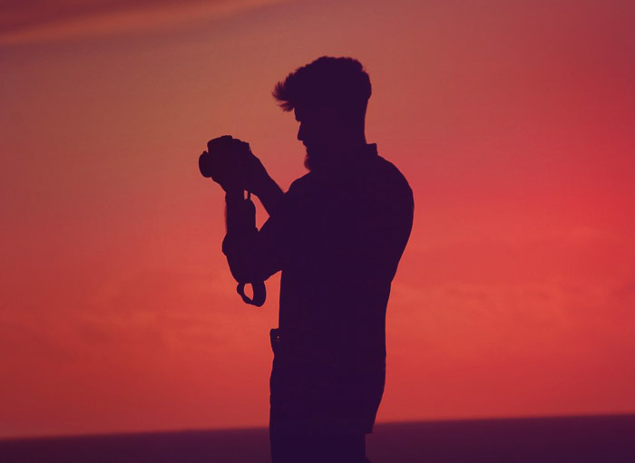 The silhouette of a photographer against a stunning orange sky