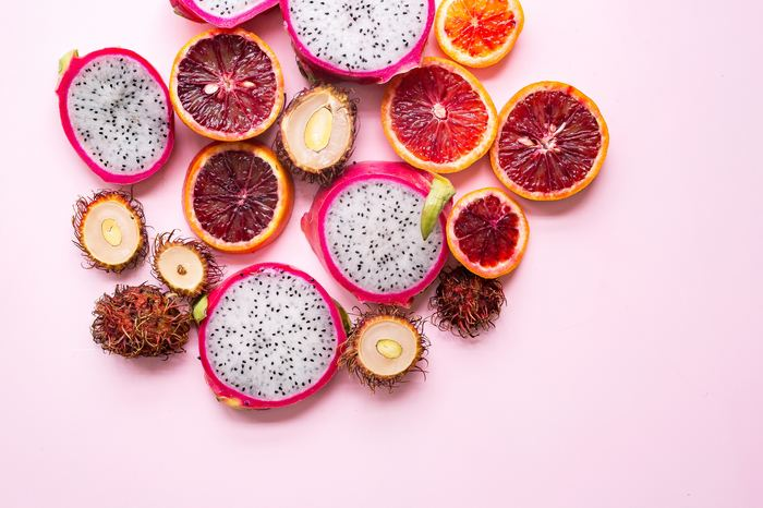 A flat lay of brightly colored fruit on a pink background - color temperature tips