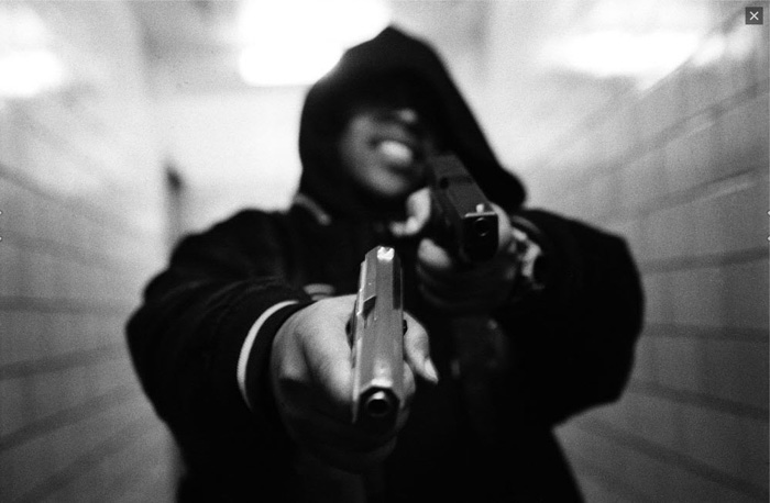A portrait of a hooded man holding two guns by contemporary street photographer Boogie (Vladimir Milivojevich)