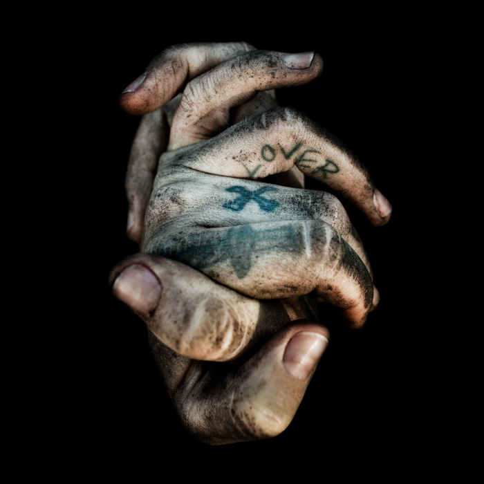 A close up portrait of tattooed hands on black background by Lee Jefferies - contemporary street photographers