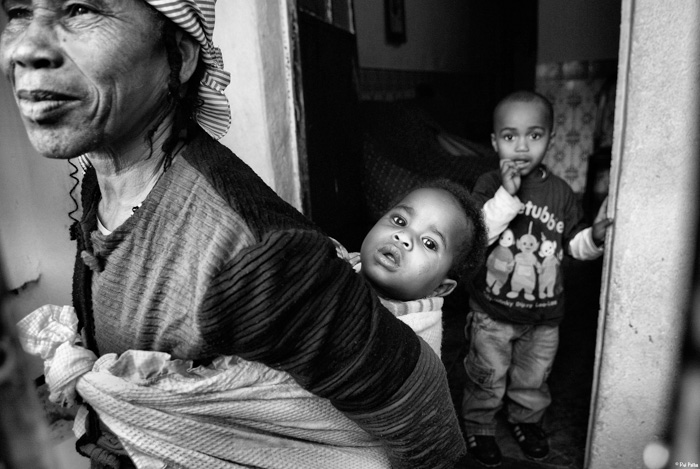 A black and white portrait of a woman with two children by Rui Palha - contemporary street photographers