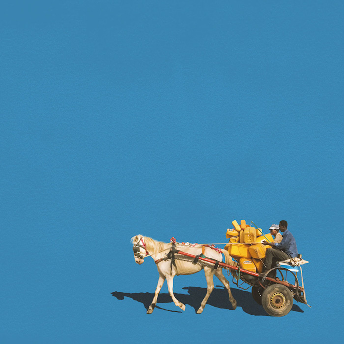 Men on a horse and cart against a block blue background by Girma Barta
