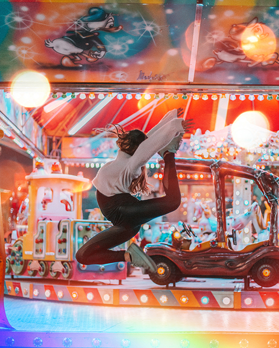 A female dancer in mid air in front of a carousel