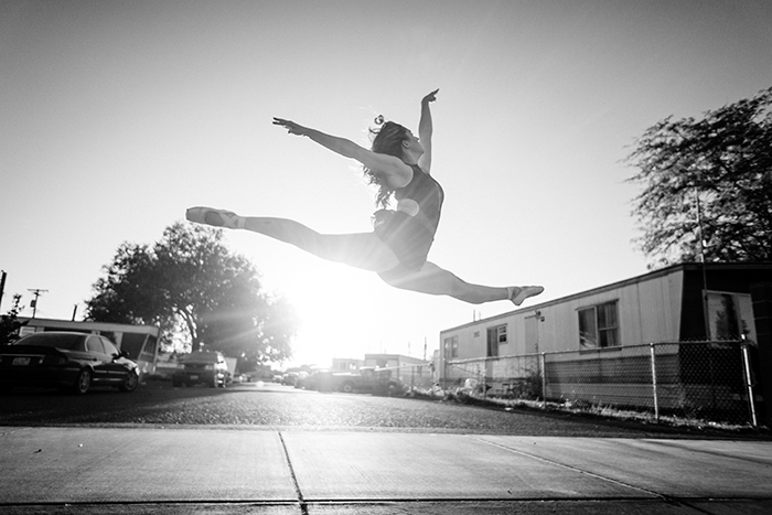 A black and white dance photography shot of a female ballet dancer mid jump