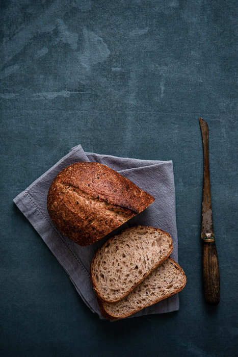 A loaf of bread shot on a rustic diy food photography backgrounds