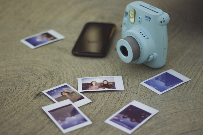 An instant camera and printed photos on a wooden table - DIY photo both ideas