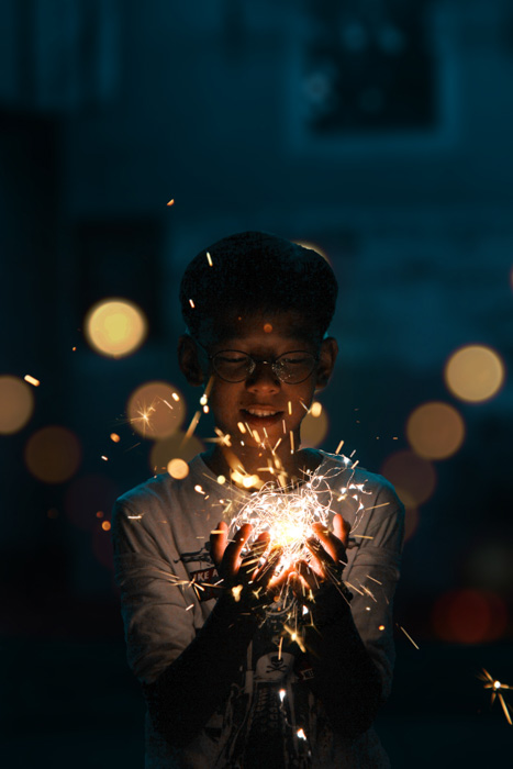 A portrait of a young boy holding a string of flickering lights shot using a DIY photo booth