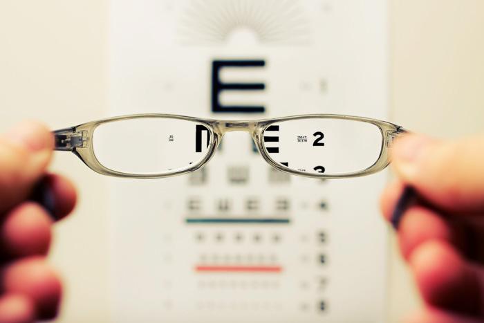 An opticians eye test chart seen through a pair of eyeglasses