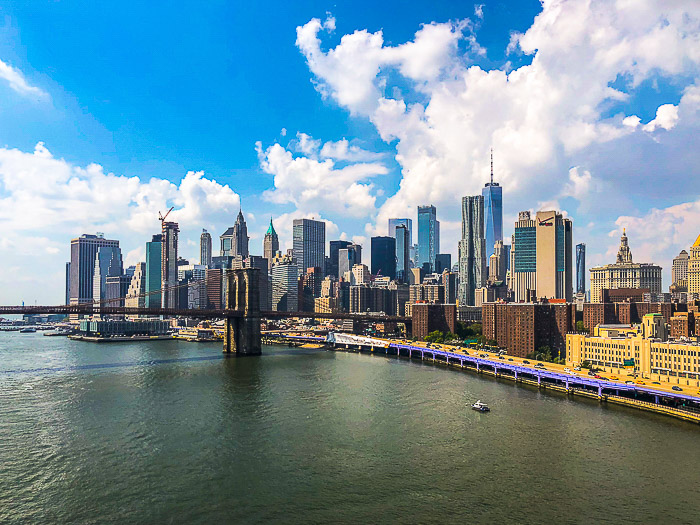 A coastal cityscape under fluffy white clouds and blue sky photography