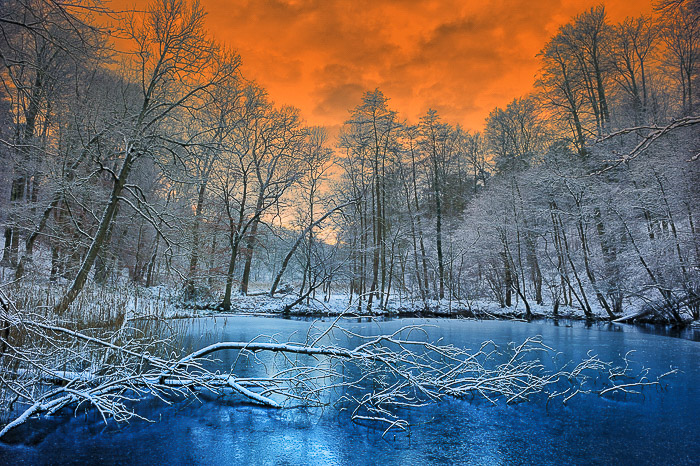 A lake surrounded by icy trees and a stunning orange sky - dramatic skies photo