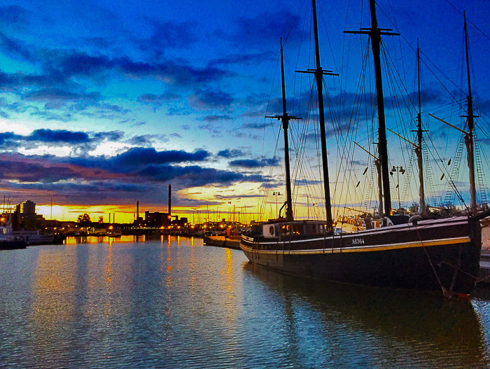 Boats docked in a harbour under a stunning evening sky - dramatic sky photography