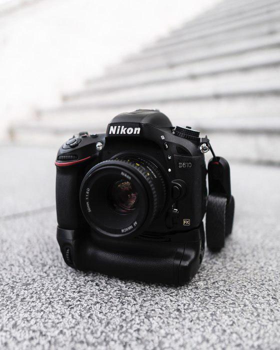 A nikon dslr camera resting on a pavement