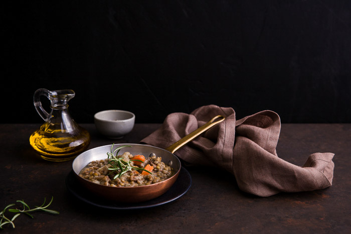 Rustic pan of cooked food, surrounded by food photography props
