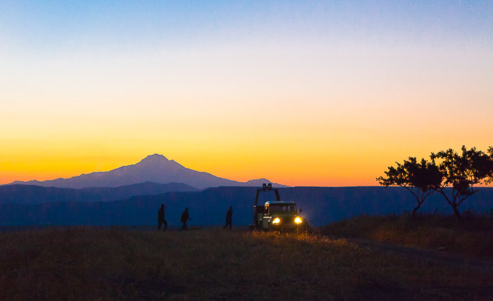 A mountains evening landscape with the silhouettes of photographers preparing to take hot air balloon photos