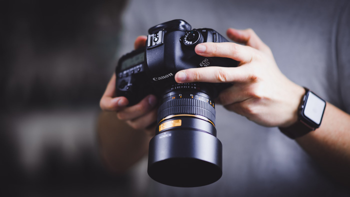 A photographer holding a Canon DSLR - what is the hot shoe in photography?