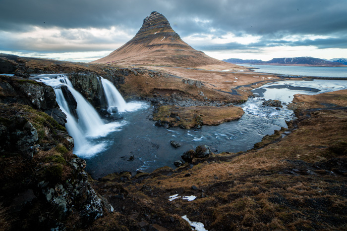 A stunning mountainous landscape with waterfalls - iconic places to photograph in Iceland