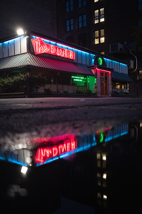 The red neon signs of a diner reflected in a puddle below - neon light photography