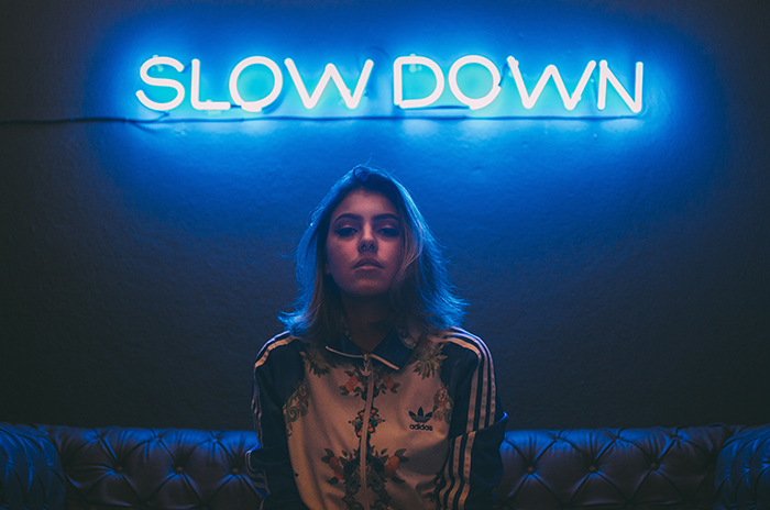 A female model sitting under blue neon signs reading 'slow down'.