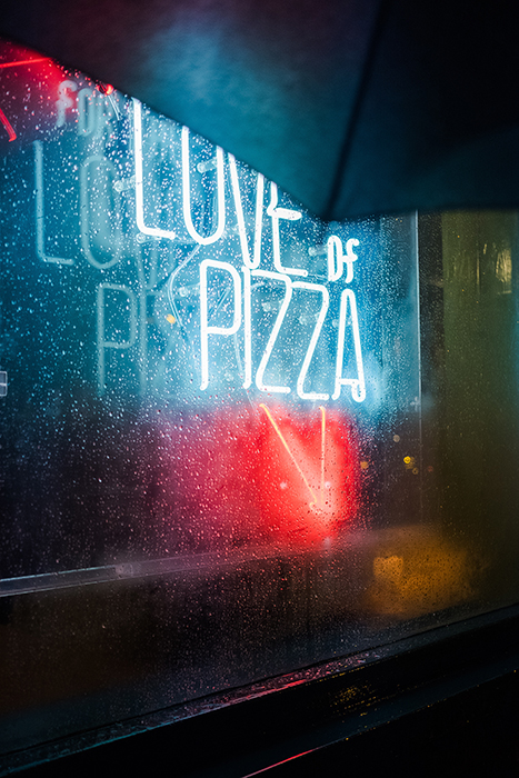 Neon signs shot through a rainy window
