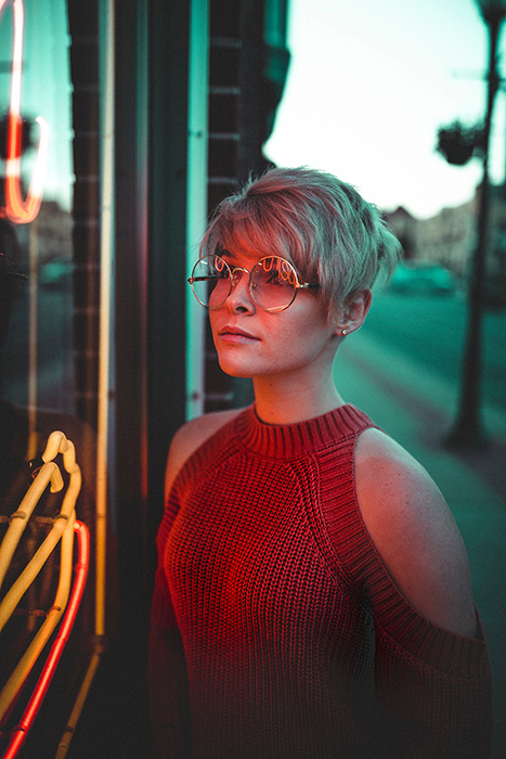 A female model facing neon signs outdoors - neon photography tips
