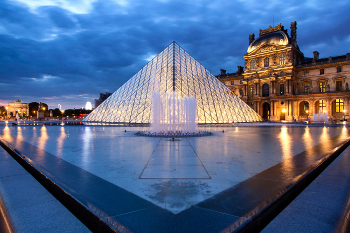 The exterior of the Louvre at night.