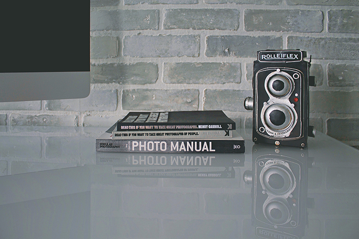 A still life featuring photography books and a rolliflex camera on a table