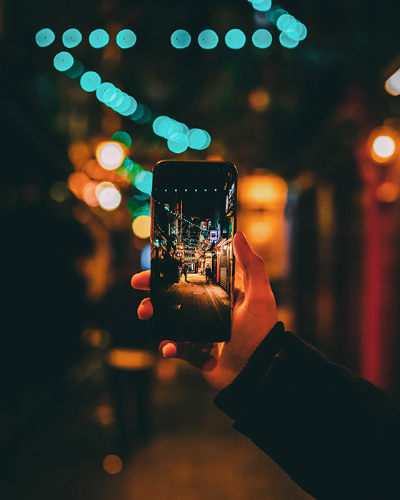A person taking a photo of a street at night using a smartphone - photography challenges