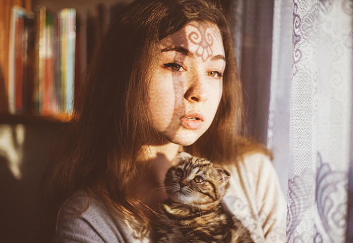 A portrait of a female model holding a cat by a window - photography projects