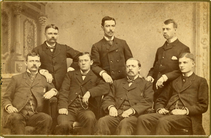 An old group photo of seven men illustrating why didn't people smile in old photos
