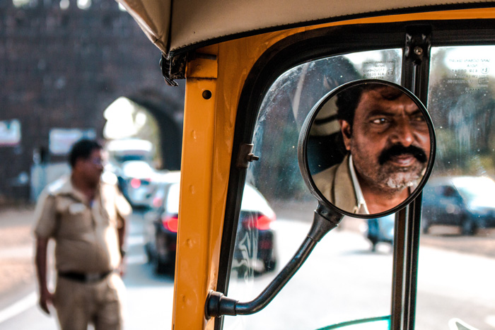 A street photography portrait of a man reflected in a car mirror - photo challenge ideas