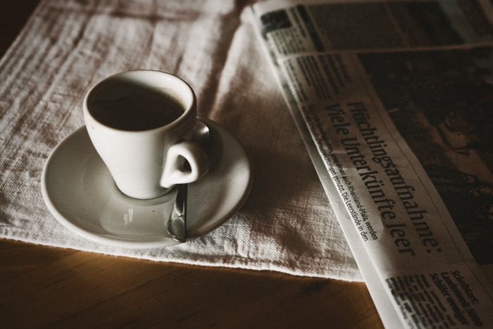 A still life photo of a coffee cup and newspaper on a table - photography challenge tips