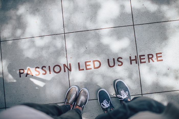 Two people standing on a pavement which has the words 'passion led us here' on the concrete - photo series ideas