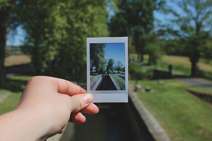 A hand holding a polaroid photo of a landscape withing a landscape - photography ideas